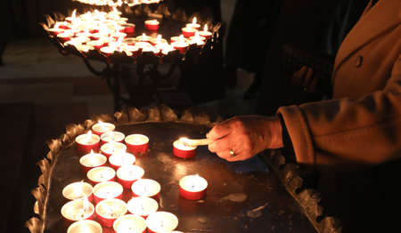 candles with flickering flame in the place of worship during the religious ceremony and an old woman