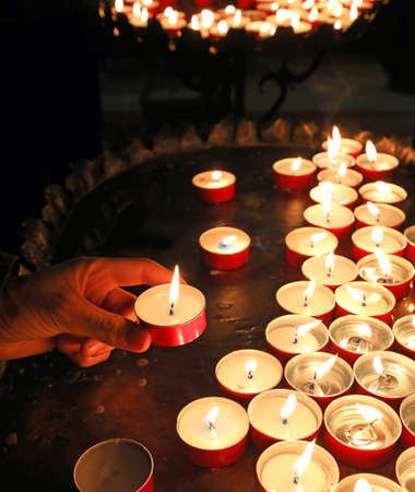 candles with flickering flame in the place of worship during the religious ceremony and an hand of boy