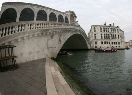 famous bridge in Venice in Italy called Ponte di Rialto photographed with wide angle lens on a cloudy day