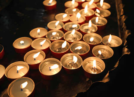 many candles with flames in the place of worship during the religious rite Stock Photo