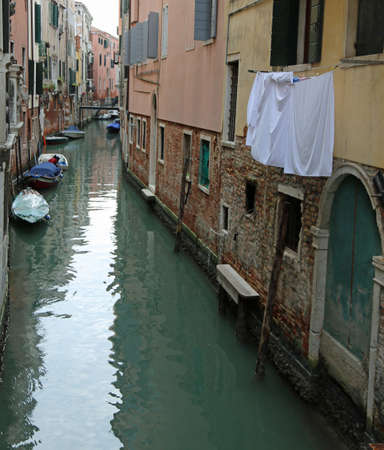 cloths hanging over a waterway with boats in the island of Venice in Italy Banco de Imagens