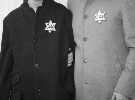 Jüdischer Vater und kleiner Sohn mit Wintermänteln und dem Symbol des Davidsterns mit dem Text Jude in Schwarz-Weiß-Effekt Standard-Bild