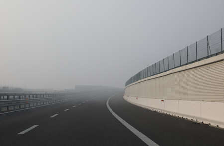 dense very dangerous fog near the curve of the highway in winter Stok Fotoğraf