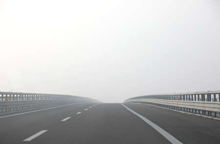 highway with very dense dangerous fog without cars during in winter