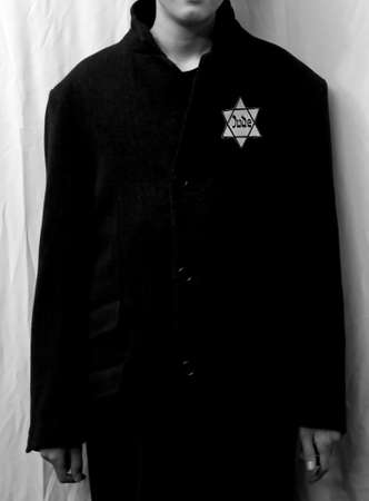 young jewish boy with winter coat and the star of David with the word Jude with balck and white effect