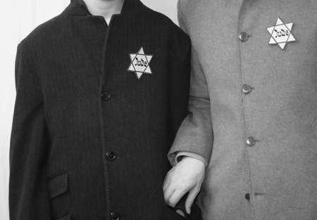 Jüdische Familie mit Vater und kleinem Sohn mit alten Mänteln und dem Symbol des Davidsterns mit dem Text Jude in Schwarz-Weiß-Effekt
