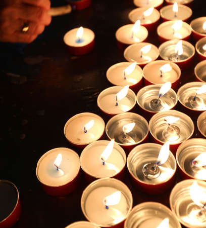 many candles with flickering flame in the place of worship during the religious ceremony