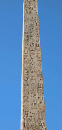 Ancient Egyptian obelisk with hieroglyphics and blue sky background