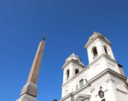 Ancient Egyptian obelisk with hieroglyphs and Trinity Church of the mountains in Rome in Italy