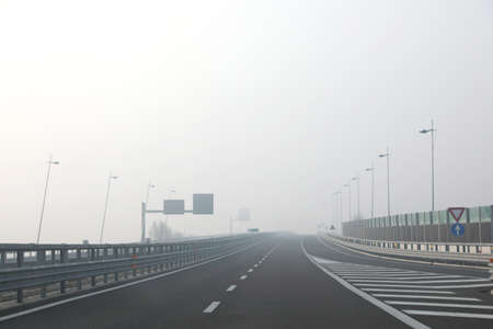 junction of the highway with very dense dangerous fog in winter