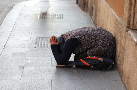 Elderly gypsy woman asking for alms kneeling on the ground with her hands clasped in supplication on the road