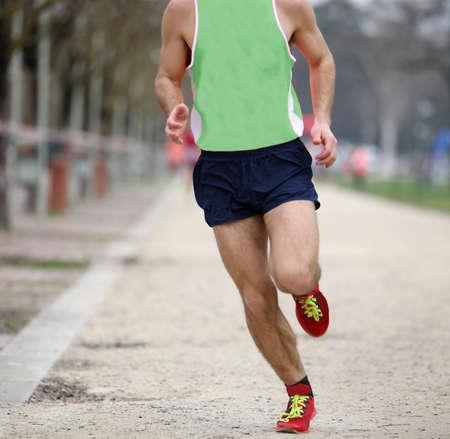 runner runs at country road race with green t-shirt and black shorts Stockfoto