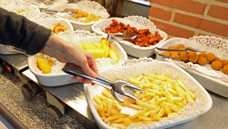 little girl's hand taking the yellow chips in the self-service restaurant Фото со стока