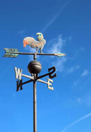 old wind vane with cock on top and cardinal points on the blue sky