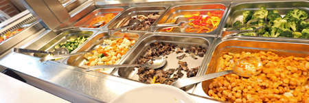 Inside a self service restaurant with many raw and cooked foods with beans and brocoli