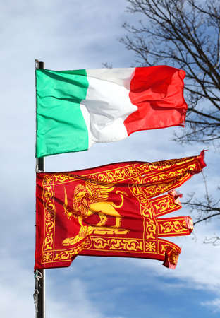 Venice, VE, Italy - January 4, 2019: Italian flag and the Flag of Veneto Region with winged Lion