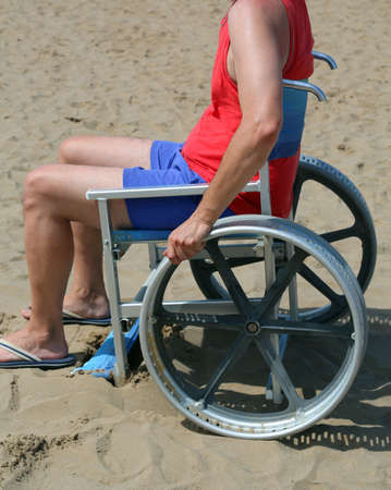 Young man on the wheelchair in the sandy beach in summer Stock fotó