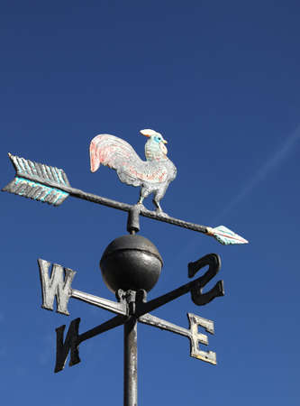 old wind vane with cock on top and cardinal points on the sky