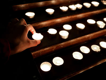 hand with many candles with the flame in the place of worship during prayer 免版税图像 - 120333856