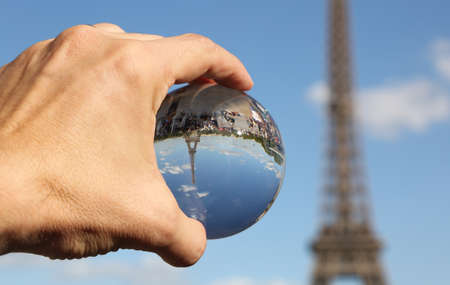 Crystal Sphere on the hand and the Eiffel Tower in Paris France