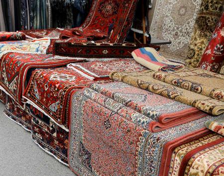 Muchas alfombras a la venta en el puesto del mercado.