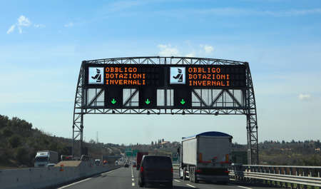big electronic road sign with text that means Winter Equipment Obligation in italian language and the police symbol in the motorway in Italy