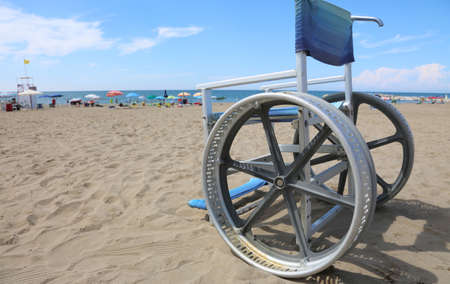 special wheelchair on the sandy beach in summer on the resort