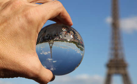 Big Crystal Sphere on the hand of a man and the Eiffel Tower in Paris France