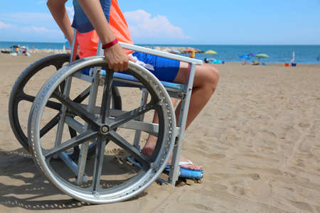 anonimous young boy on the wheelchair on the beach
