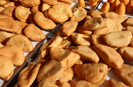 typical Italian food called Panzerotti maked with mozzarella cheese and tomato for sale at stand