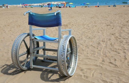 special wheelchair with big wheels on aluminium on the beach in summer