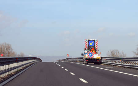 truck with big road sign with arrow on the motorway before the roadworks Imagens