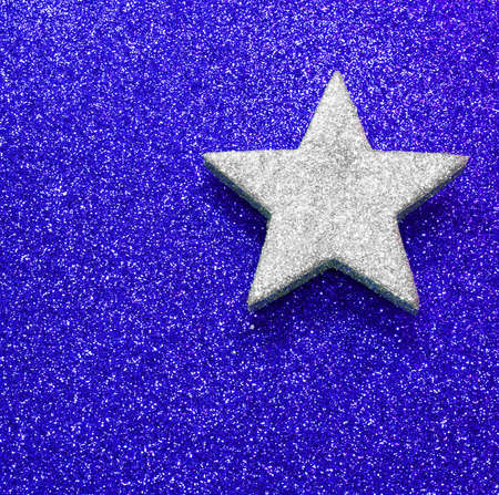silver star on blue bright background glowing