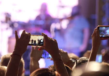 many people at live concert with smartphones near the stage Фото со стока
