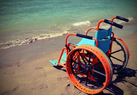 Silla de ruedas naranja en la playa sin gente en verano con efecto de tono antiguo