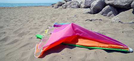 broken colored abandoned  parasol at the sandy beach after the storm
