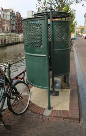 modern public urinal on a street near the navigable canal in Amsterdam Netherlands Foto de archivo