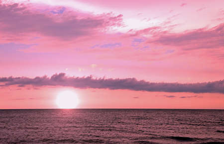 landscape with sun at sunset and pink clouds over the ocean Imagens - 121874581