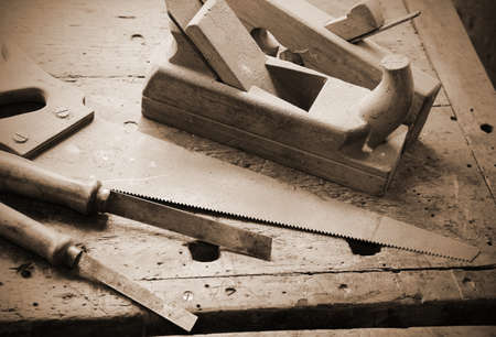 planers and chisels and an hand saw on the wooden Workbench with old toned sepia effect