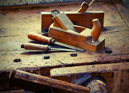 two old planes and two chisels over the work table with the old wooden vise used in the carpenter's shop