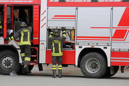 Rome, RM, Italy - May 10, 2018: red fire truck and talian firefighters with uniform during fire drill. The big text Vigili del fuoco in the uniform means Firemen in Italian language Editorial