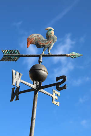 vintage weathercock in iron on blue sky background
