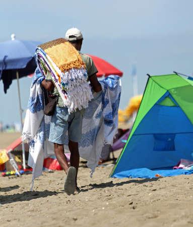 vendeur de rue marche sur la plage pour vendre les nombreux tapis qu'il porte sur son épaule Banque d'images