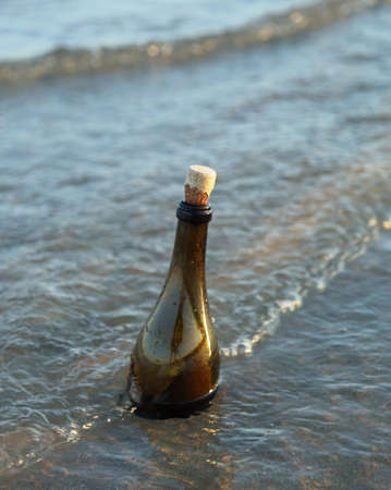 glass bottle with cork cap and a secret message on the beach and the water of ocean