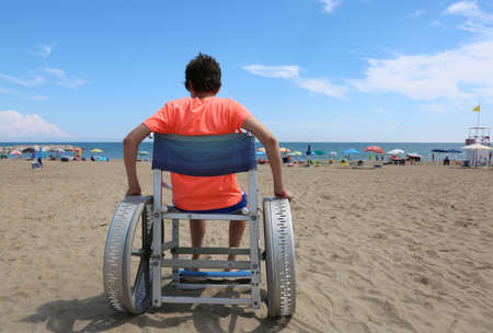 young boy on the wheelchair on the beach in summer
