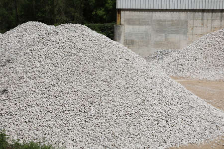 high pile of stones in a quarry specialized in gravel extraction