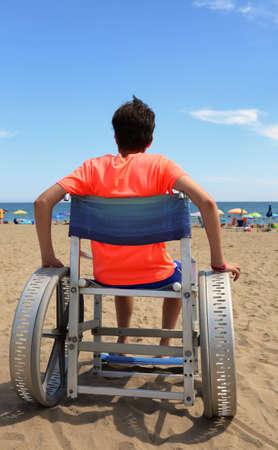 boy on wheelchair with big aluminum wheels on the beach near the sea in summer