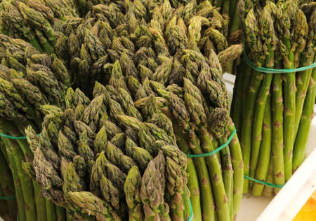 bundles of tips of green asparagus for sale at market