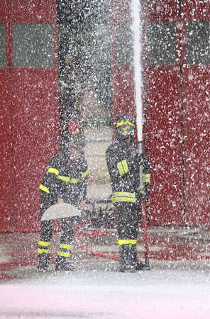 two firefighters during an exercise in the fire station and the foam spilled around