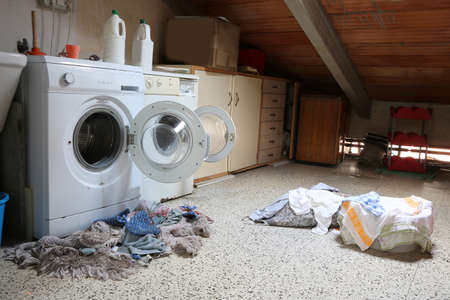 Inside a dusty attic of a school with two big washing machines and tatters dirty
